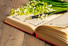 Flowers lily of the valley on the book for records and a pen Royalty Free Stock Image
