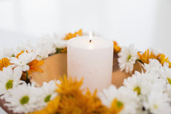 Flowers and a lit candle Stock Images