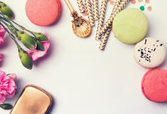 Flowers, macarons, paper straws in pastel color and golden box Royalty Free Stock Photo