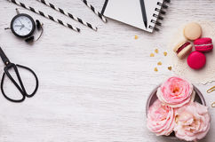 Flowers, macarons, striped paper straws and other cute stuff. On white table, top view Stock Images