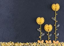 Flowers made out of various pasta on the dark slate background, topview. Flowers made from pasta.  stock images