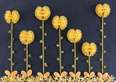 Flowers made out of various pasta on the dark slate background, topview. Flowers made from pasta. Flowers made out of various pasta on the dark slate background royalty free stock photography