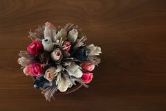 Paper flowers in the pot on the wooden table stock photo