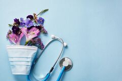 Flowers with mask and stethoscope on blue background. Happy nurse day concept. Top view