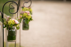 Flowers in mason jars at wedding ceremony. Pink and green flowers in glass mason jars along a ceremony line at a wedding Stock Photo