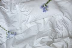 Flowers on the messy bed, white bedding items and blue flowers bouqet stock photo