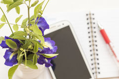 Flowers and mobile with notebook on table white Royalty Free Stock Photography