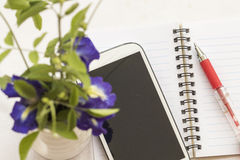 Flowers and mobile with notebook on table white Royalty Free Stock Photos