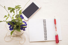 Flowers and mobile with notebook on table white Stock Image
