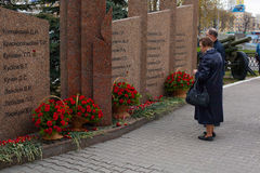 The flowers at the monument to the fallen. An elderly couple laying flowers to the memorial of the fallen in the war Stock Photos