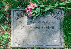 Flowers on Mothers Grave Marker. Grave marker in cemetery with flowers for concept of death and loss Royalty Free Stock Photography