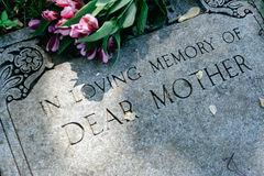Flowers on Mothers Grave Marker. Grave marker in cemetery with flowers for concept of death and loss Royalty Free Stock Photo