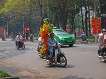 Flowers on Motorbike. A man riding on a bike with flowers behind. Ideal for writeup & news coverage concerning Vietnam Stock Photos