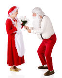 Flowers for Mrs. Claus. Santa giving a bouquet of white poinsettias to Mrs. Claus. Isolated on white stock photography