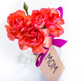Flowers for mum on Mothers day. Orange carnations in a bunch with a sign for mom for mothers day Stock Photography