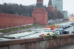 The flowers near a place of murder of the politician Boris Nemtsov and the car of police protecting the Kremlin from march of oppo Royalty Free Stock Images