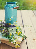Flowers near watering can with old books on a rustic wooden tabl Royalty Free Stock Photos