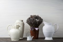 Flowers in neutral colored vases, candles on rustic wooden shelf against shabby white wall. Home decor. Home decorations in the interior. On the wooden stock photos