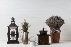 Flowers in neutral colored vases, candles on rustic wooden shelf against shabby white wall. Home decor. Home decorations in the interior. On the wooden royalty free stock images