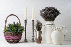 Flowers in neutral colored vases, candles on rustic wooden shelf against shabby white wall. Home decor. Home decorations in the interior. On the wooden royalty free stock photography