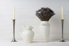 Flowers in neutral colored vases, candles on rustic wooden shelf against shabby white wall. Home decor. Home decorations in the interior. On the wooden stock photography