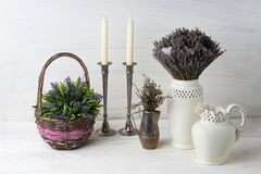 Flowers in neutral colored vases, candles on rustic wooden shelf against shabby white wall. Home decor. Home decorations in the interior. On the wooden royalty free stock image