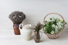 Flowers in neutral colored vases, candles on rustic wooden shelf against shabby white wall. Home decor. Home decorations in the interior. On the wooden royalty free stock photos