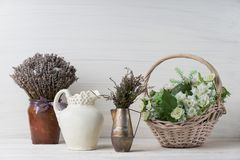 Flowers in neutral colored vases, candles on rustic wooden shelf against shabby white wall. Home decor. Home decorations in the interior. On the wooden stock images