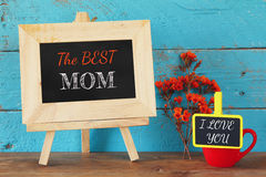 Flowers next to blackboard with phrase: THE BEST MOM, and the small blackboard with phrase: I LOVE YOU. on wooden table Royalty Free Stock Image