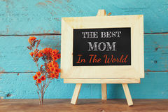 Flowers next to blackboard with phrase: THE BEST MOM IN THE WORLD, on wooden table. happy mother's day concept Royalty Free Stock Photo
