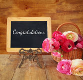 Flowers next to blackboard with phrase: congratulations Stock Photography