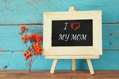 Flowers next to blackboard with phrase: I LOVE MY MOM, on wooden table. happy mother's day concept Royalty Free Stock Photos