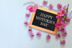 Flowers next to blackboard with phrase on wooden table. happy mother's day concept Stock Photo