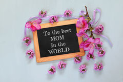 Flowers next to blackboard with phrase on wooden table. happy mother's day concept Stock Images