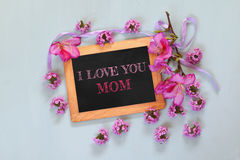 Flowers next to blackboard with phrase on wooden table. happy mother's day concept Stock Photography