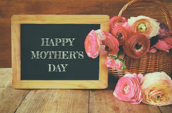 Flowers next to blackboard, on wooden table. mother's day concep Royalty Free Stock Image