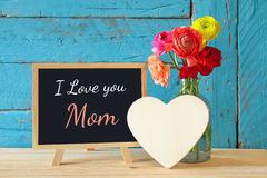 Flowers next to blackboard, on wooden table. mother's day concep Royalty Free Stock Photo
