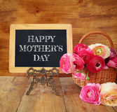 Flowers next to blackboard, on wooden table. mother's day concep Royalty Free Stock Photography