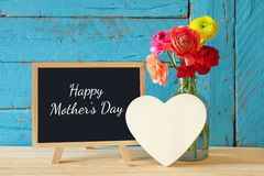 Flowers next to blackboard, on wooden table. mother's day concep Stock Image