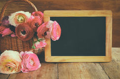 Flowers next to empty blackboard, on wooden table. copy space Royalty Free Stock Images