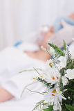 Flowers next to woman about to get surgery Stock Photography