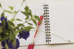 Flowers with notebook on table white Stock Photography