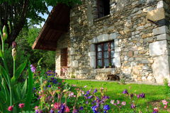 Flowers and old house. Beautiful flowers and garden with a stone-built house in the the french countryside (chartreuse Royalty Free Stock Images