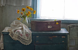 Flowers and old suitcase. Bouquet of flowers and old suitcase on a table Royalty Free Stock Photo