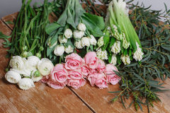 Flowers on a old wooden table. Florist workspace: man making floral decorations. Flowers on a old wooden table. Florist workspace: man making floral decorations Royalty Free Stock Photos