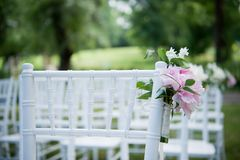 Flowers on outdoor wedding chairs royalty free stock image