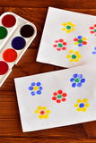 Flowers painted children's fingers. Two drawings, paint on a brown wooden background. A children drawing. Children creativity. Children earlier development stock images