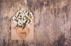 Flowers in a paper envelFlowers in a paper envelope and a wooden heart. Copy spaceope and a wooden heart. Copy space. Flowers in a paper envelope and a wooden Royalty Free Stock Images