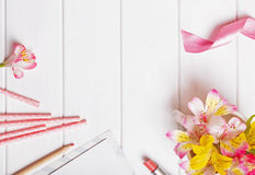 Flowers, paper straws, pink ribbon and other cute objects. On the white wooden table, top view Stock Image