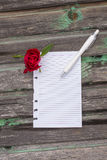 Flowers and paper on wooden background. Pencil Stock Photo